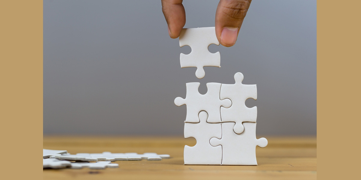 Image of a hand holding a puzzle piece above the position it goes into several other pieces that have already been connected.