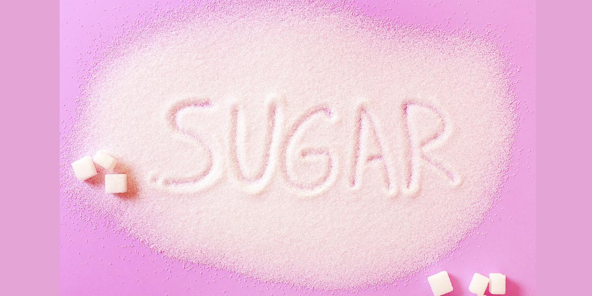 """White sugar on the table with the word """"sugar"""" carved in it."""