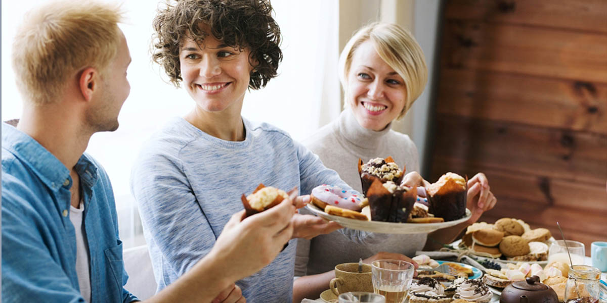 Several friends sitting at a table next to one another sharing a plate of baked goods containing muffins, cookies and other sweet treats.