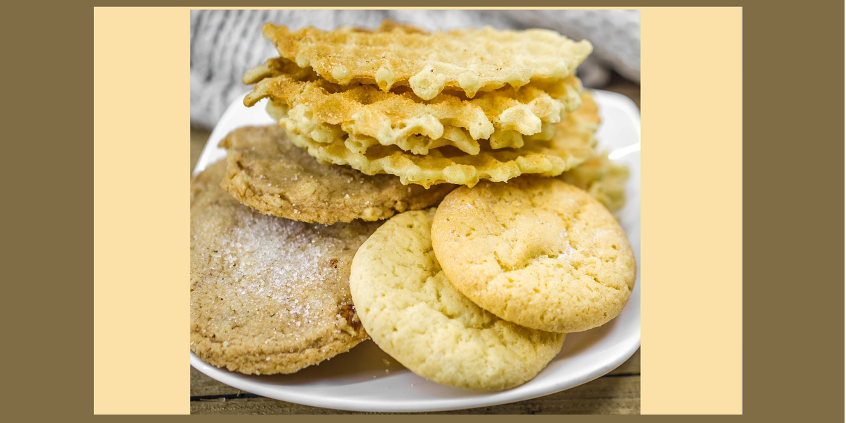 Image of a plate of delicious cookies and a cup of hot tea with a cinnamon stick and a spoonful of brown sugar on wooden background, conveying a holiday concept and warm mood